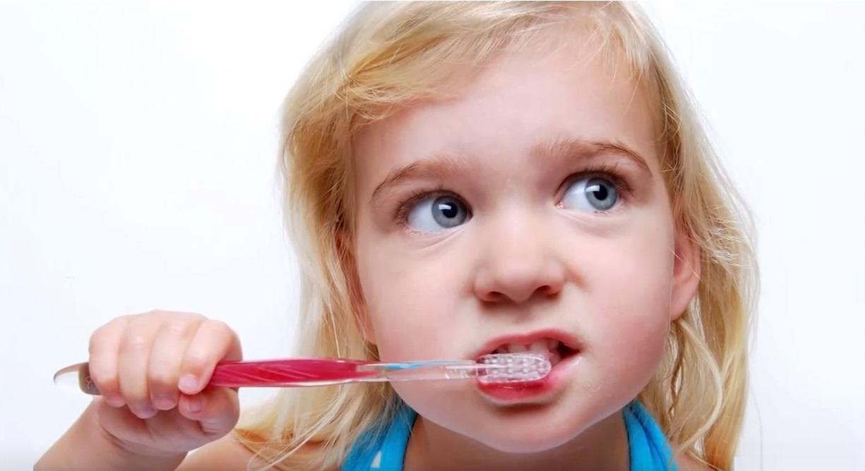 child brushing teeth blue eyes toothbrush