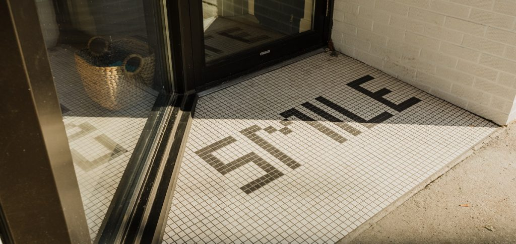 front entrance mosaic tile spelling out the word smile at dental office