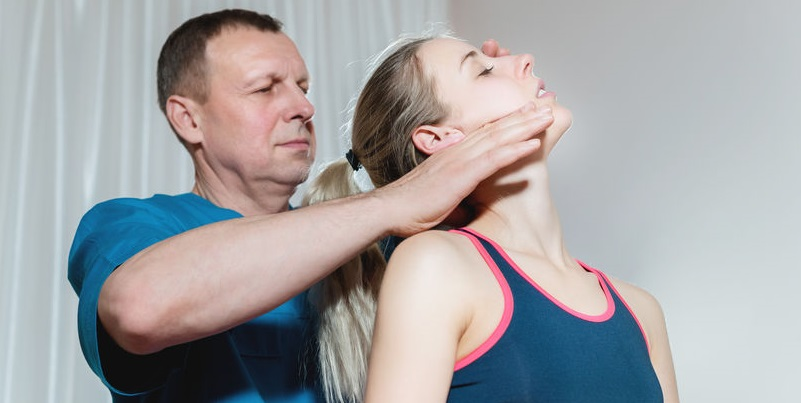 certified physiotherapist massages the temporomandibular joint (TMJ) bones and muscles, manual therapy.